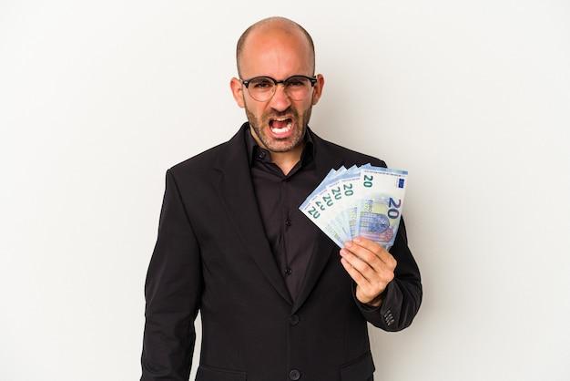 Jeune homme chauve tenant des factures isolées sur fond blanc criant très en colère et agressif.