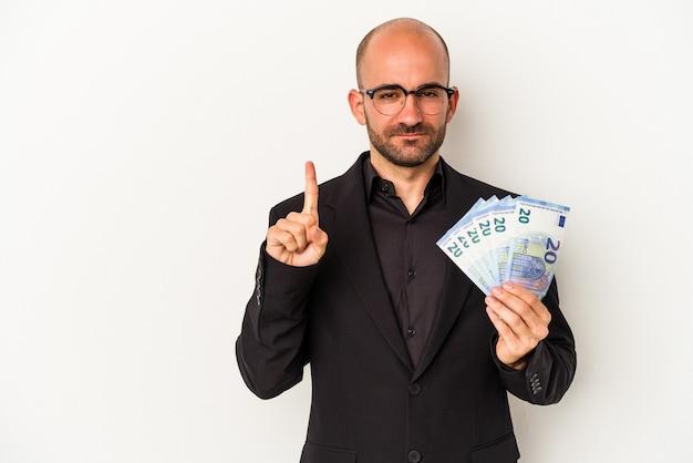 Jeune homme chauve tenant des factures isolées sur fond blanc montrant le numéro un avec le doigt.
