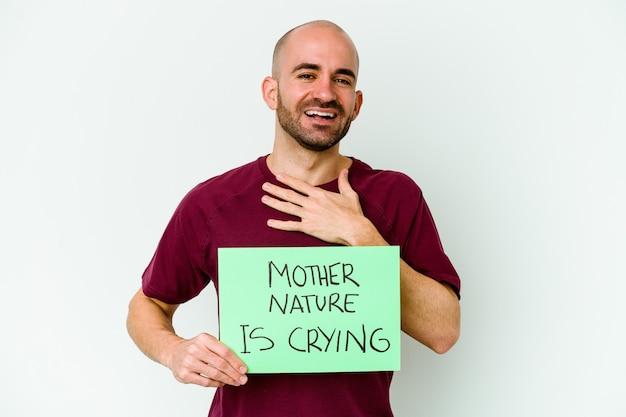 Jeune homme chauve tenant une mère nature pleurer isolé sur un mur blanc rit fort en gardant la main sur la poitrine