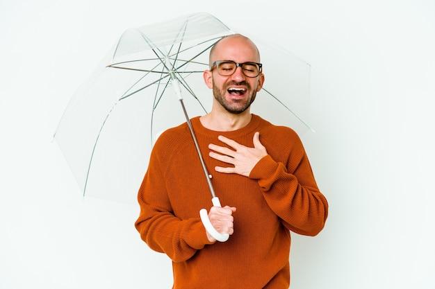 Jeune homme chauve tenant un parapluie isolé rit fort en gardant la main sur la poitrine