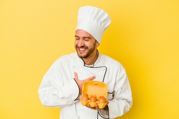 Jeune homme de chef caucasien tenant des oeufs isolés sur le mur jaune éclate de rire en gardant la main sur la poitrine.