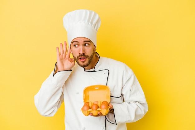 Jeune homme de chef caucasien tenant des oeufs isolés sur un mur jaune en essayant d'écouter un commérage.