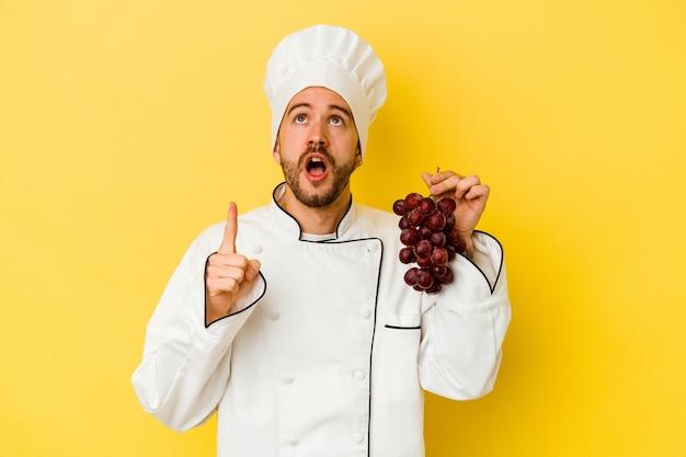 Jeune homme de chef caucasien tenant des raisins isolés sur un mur jaune pointant vers le haut avec la bouche ouverte.