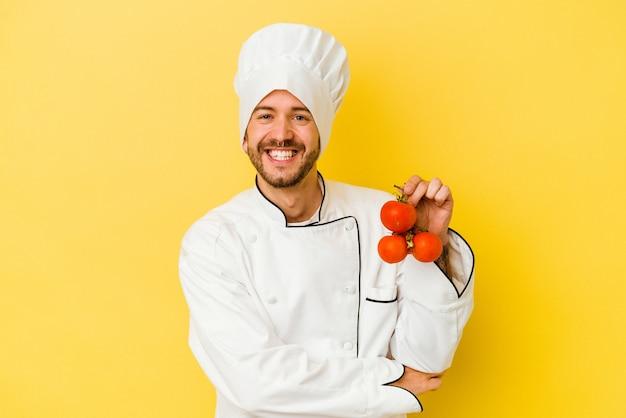 Jeune homme de chef caucasien tenant des tomates isolées sur un mur jaune en riant et en s'amusant.