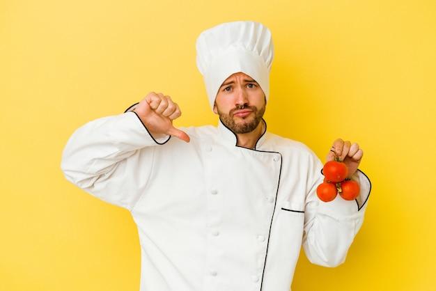 Jeune homme de chef caucasien tenant des tomates isolées sur un mur jaune se sent fier et confiant, exemple à suivre.