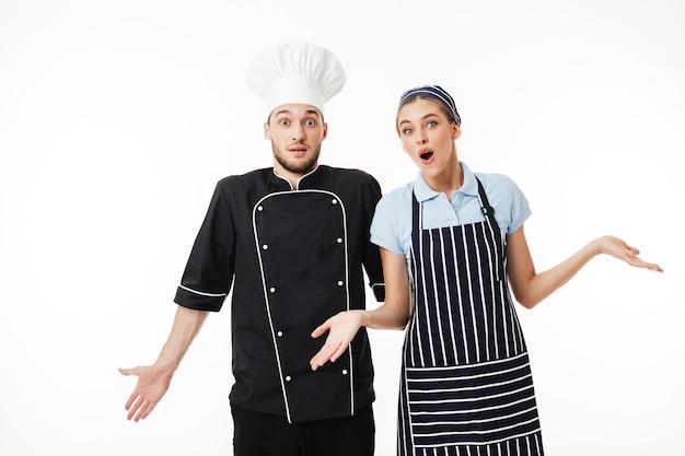 Jeune homme chef en uniforme noir et chapeau blanc et femme cuisinier en tablier rayé et casquette avec étonnement