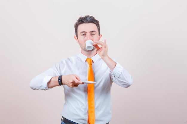 Jeune homme en chemise blanche, cravate buvant du café turc