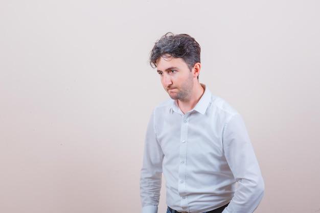 Jeune homme en chemise blanche en détournant les yeux en pensant et en ayant l'air désespéré