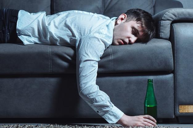 Jeune homme en chemise blanche dormant sur l'entraîneur avec une bouteille de bière verte