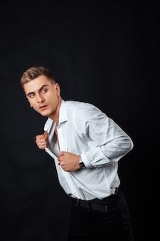 Un jeune homme en chemise blanche sur fond noir.