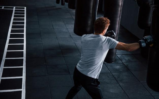 Jeune homme en chemise blanche et gants de protection de boxe faisant des exercices en salle de sport avec sac de poussée.
