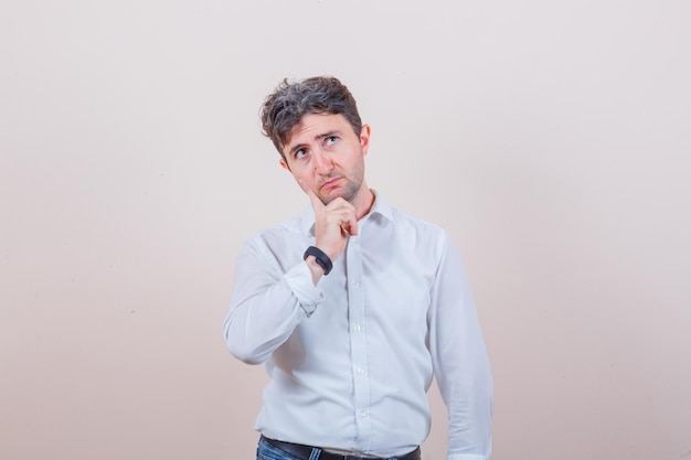 Jeune homme en chemise blanche, jeans et à la réflexion