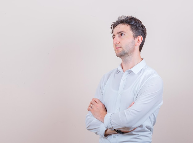 Jeune homme en chemise blanche levant les bras croisés et à la réflexion