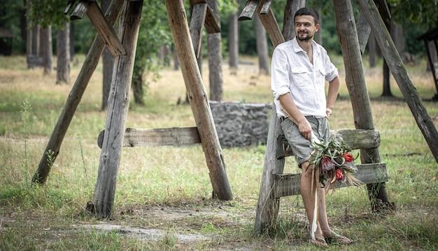 Jeune homme en chemise blanche tenant un bouquet de fleurs exotiques, concept de rencontres.