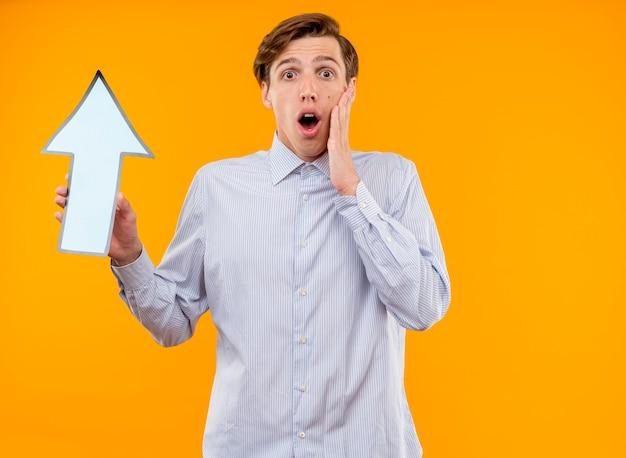 Jeune homme en chemise blanche tenant une flèche bleue regardant la caméra étonné et surpris debout sur fond orange