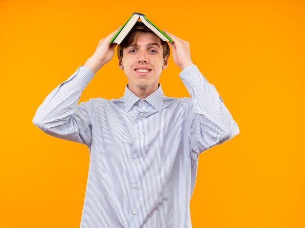 Jeune homme en chemise blanche tenant un livre ouvert au-dessus de sa tête souriant joyeusement debout sur un mur orange