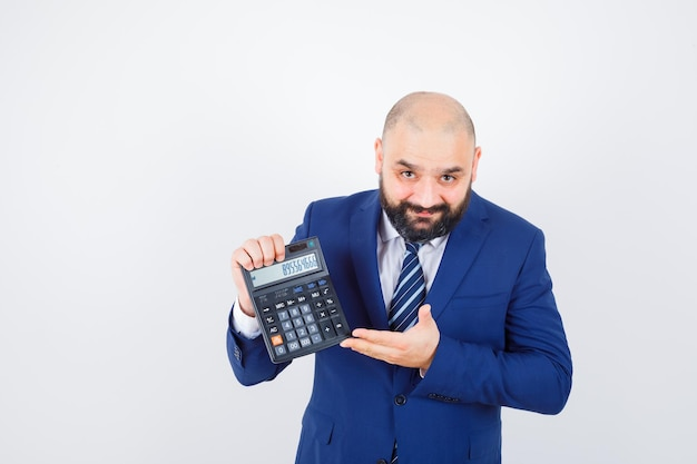 Jeune homme en chemise blanche, veste montrant une calculatrice et ayant l'air confiant, vue de face.