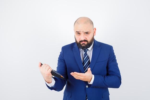 Jeune homme en chemise blanche, veste montrant la calculatrice et hésitant, vue de face.