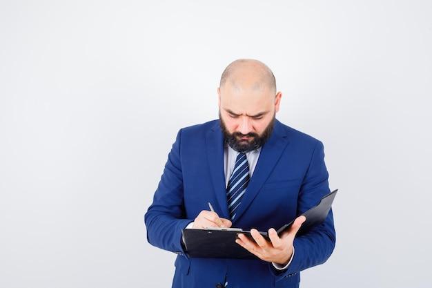 Jeune homme en chemise blanche, veste prenant des notes sur le presse-papiers et l'air occupé, vue de face.