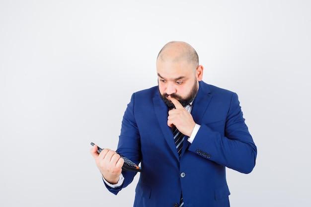 Jeune homme en chemise blanche, veste regardant la calculatrice et regardant pensif, vue de face.