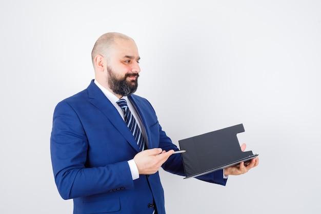 Jeune homme en chemise blanche, veste tenant un presse-papiers, un stylo et l'air confiant, vue de face.