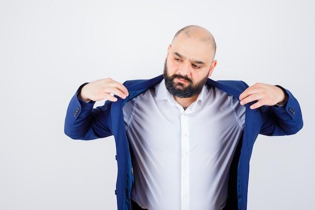 Jeune homme en chemise blanche, veste tenant son col tout en détournant les yeux et l'air élégant, vue de face.