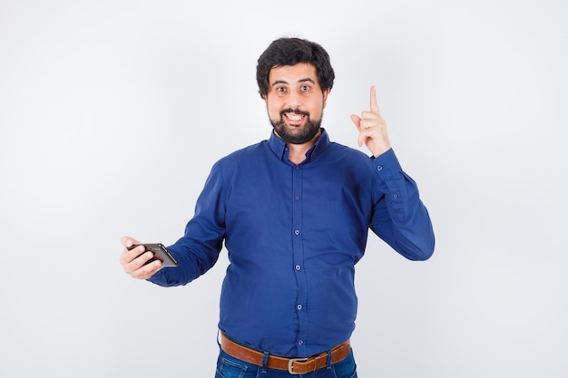 Jeune homme en chemise bleu royal tenant un téléphone tout en levant les yeux, vue de face.