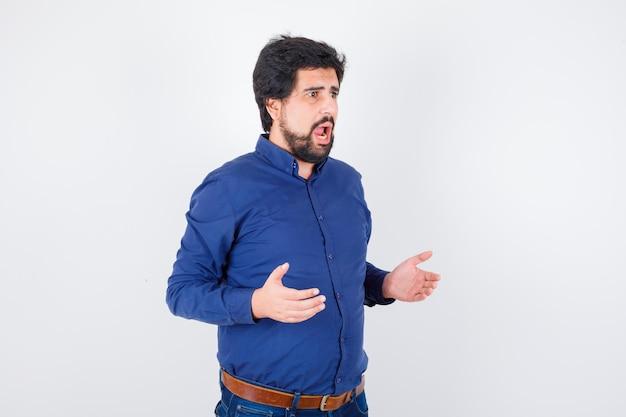Jeune homme en chemise bleue à l'air anxieux , vue de face.