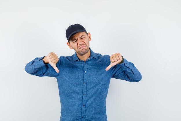 Jeune homme en chemise bleue, casquette montrant les pouces vers le bas et l'air déçu, vue de face.