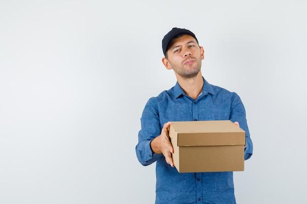 Jeune homme en chemise bleue, casquette présentant une boîte en carton, vue de face.