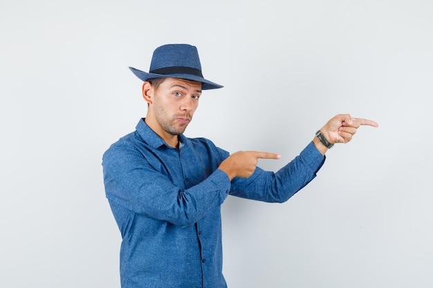 Jeune homme en chemise bleue, chapeau pointant sur le côté, vue de face.