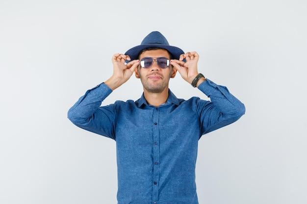 Jeune homme en chemise bleue, chapeau touchant ses lunettes et l'air joyeux, vue de face.