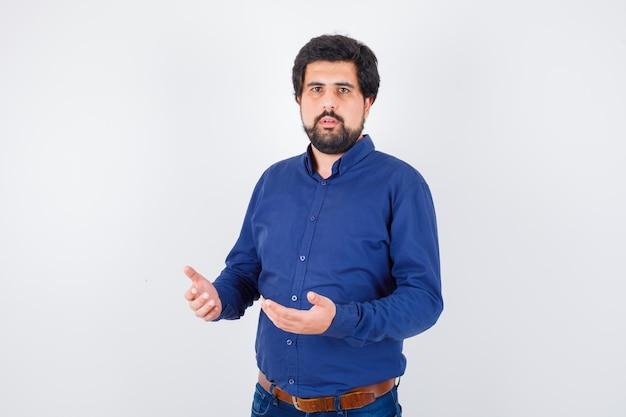 Jeune homme en chemise bleue à la confusion, vue de face.