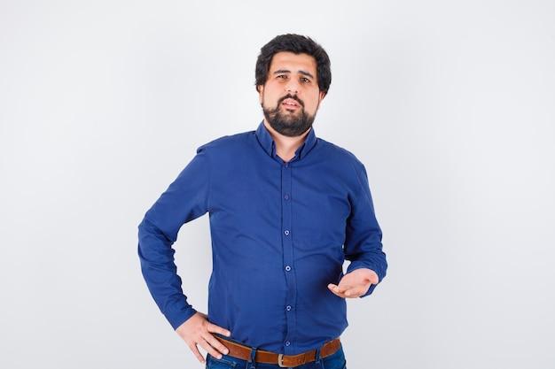 Jeune homme en chemise bleue étirant la main dans un geste perplexe et l'air confiant, vue de face.
