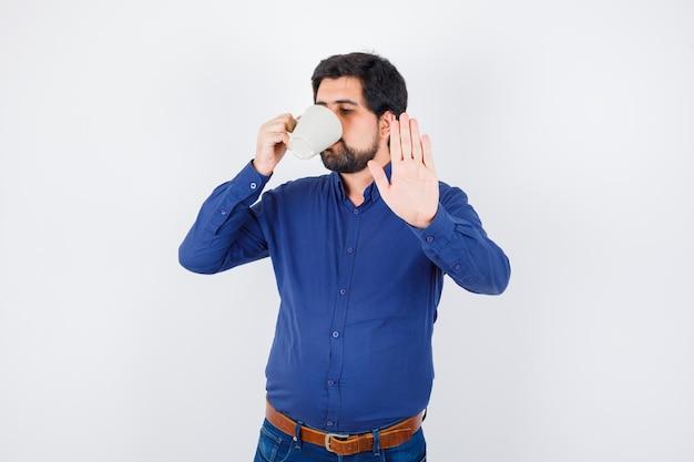 Jeune homme en chemise bleue et jeans buvant une tasse d'eau et montrant un panneau d'arrêt et ayant l'air sérieux, vue de face.