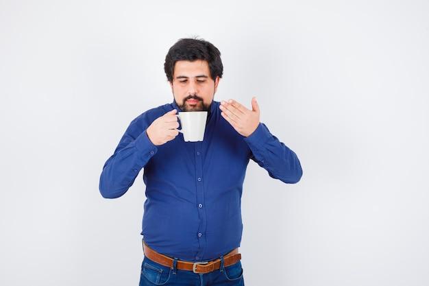 Jeune homme en chemise bleue et jeans essayant de boire une tasse d'eau et l'air sérieux, vue de face.
