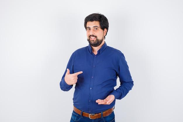 Jeune homme en chemise bleue et jeans étirant la main comme tenant quelque chose et pointant sur lui-même et l'air optimiste, vue de face.