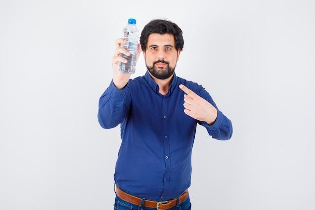 Jeune homme en chemise bleue et jeans tenant une bouteille d'eau et la pointant et l'air optimiste, vue de face.