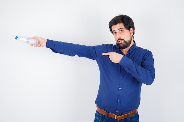 Jeune homme en chemise bleue et jeans tenant une bouteille d'eau et la pointant et semblant sérieux, vue de face.