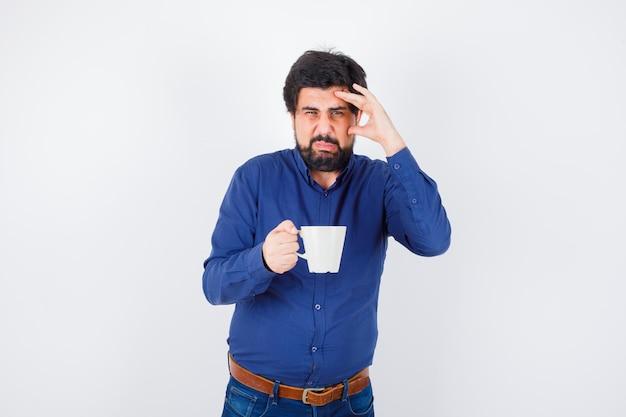 Jeune homme en chemise bleue et jeans tenant une tasse et mettant la main sur le front et l'air épuisé, vue de face.