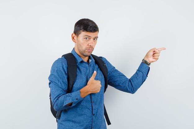 Jeune homme en chemise bleue pointant vers le côté avec le pouce vers le haut, vue de face.