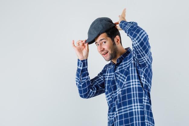 Jeune homme en chemise bleue portant une casquette et à la satisfaction.