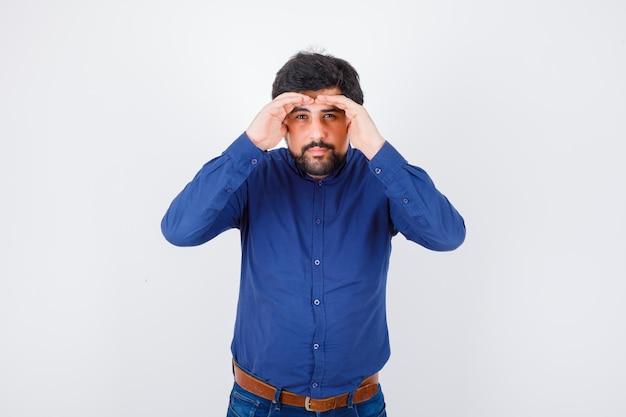 Jeune homme en chemise bleue regardant avec les mains au-dessus de la tête et regardant concentré, vue de face.