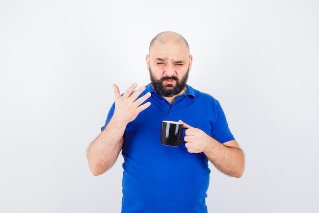 Jeune homme en chemise bleue sentant une odeur étrange, vue de face.