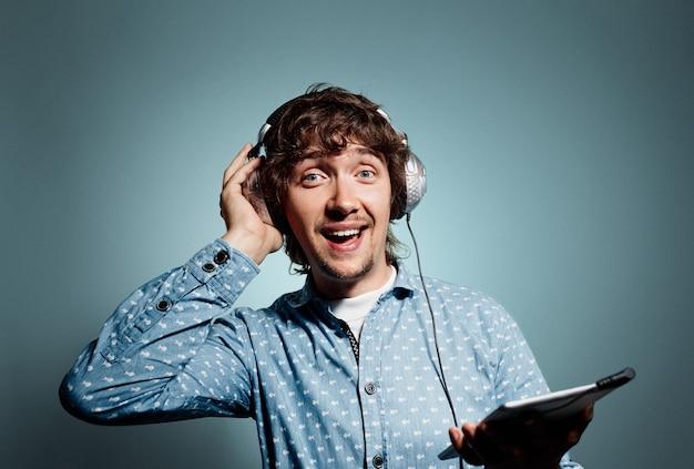 Jeune homme en chemise bleue tenant la tablette et portant des écouteurs