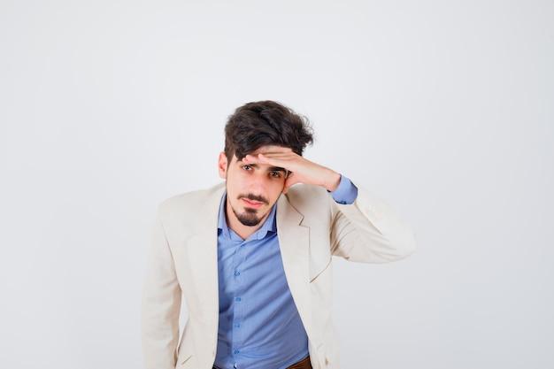 Jeune homme en chemise bleue et veste de costume blanche mettant la main sur le front et l'air sérieux