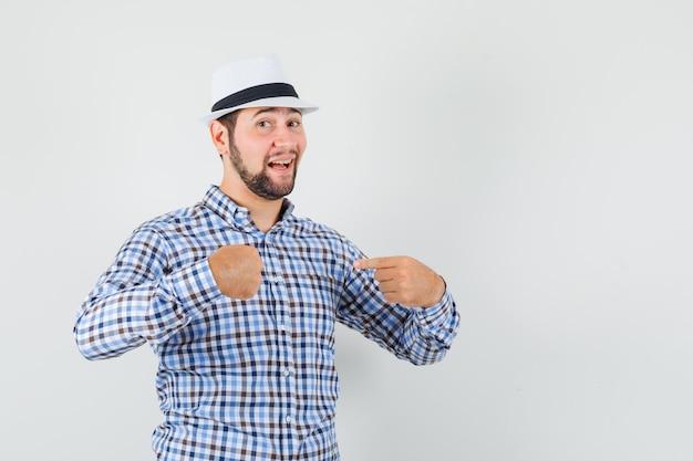 Jeune homme en chemise à carreaux, chapeau pointant du doigt sur lui-même et à la fierté, vue de face.