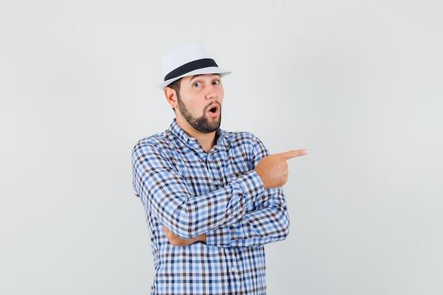 Jeune homme en chemise à carreaux, chapeau pointant vers le côté et à la surprise, vue de face.