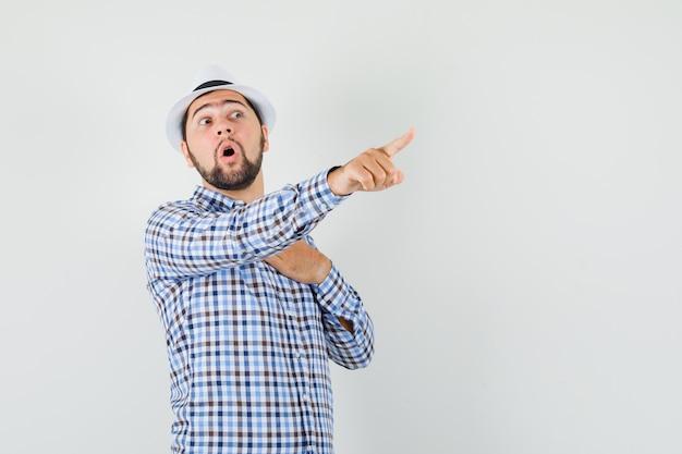 Jeune homme en chemise à carreaux, chapeau pointant vers l'extérieur, tenant la main sur la poitrine, vue de face.
