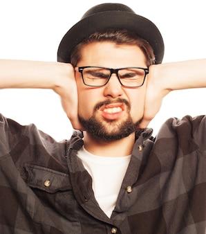 Jeune homme avec une chemise à carreaux couvrant ses oreilles avec ses mains. isolé sur blanc.